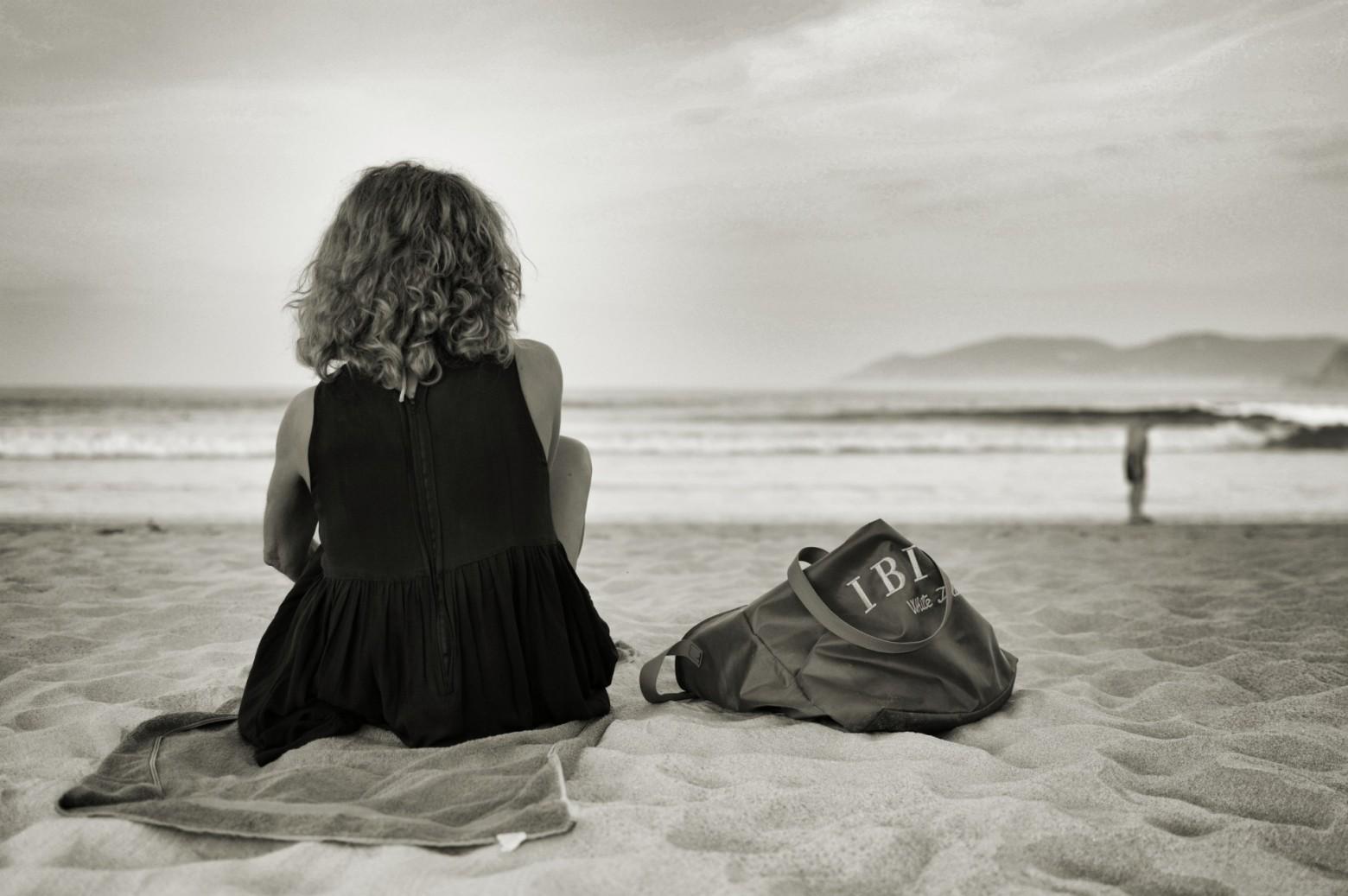 femme assise sur le sable au bord de la plage