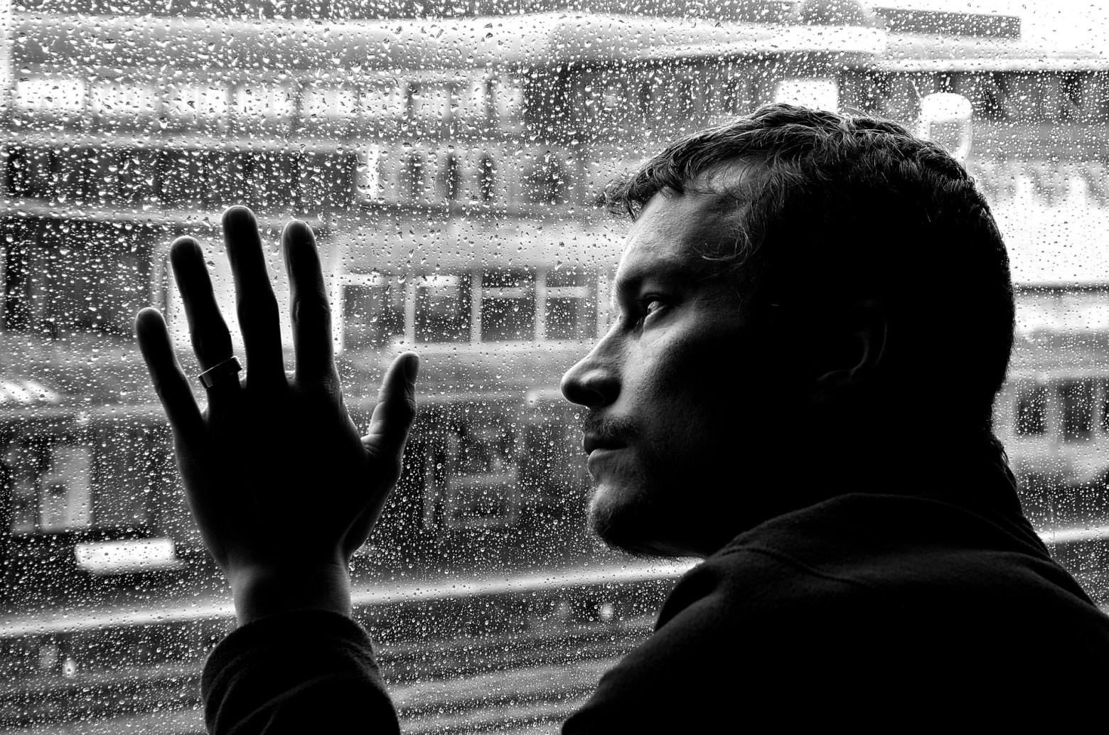 homme triste qui regarde la pluie tomber fenêtre