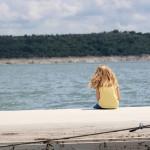 petite fille blonde assise au bord de l' eau images photos gratuites