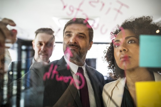 Businesspeople planning on a glass wall