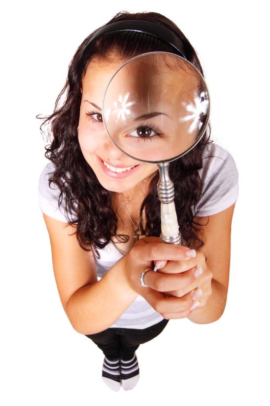 jeune femme fille qui regarde dans une loupe